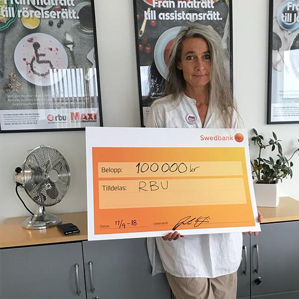 """Bild på ordförande Maria Persdotter och check med texten """"100000 kr till RBU"""""""