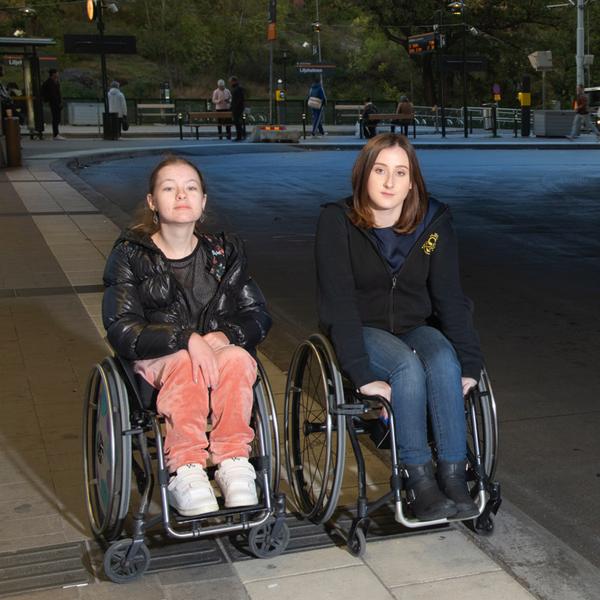 Kompisarna Bea Lindholm och Nicola St Clair Maitland i rullstolar vid Liljeholmens centrum
