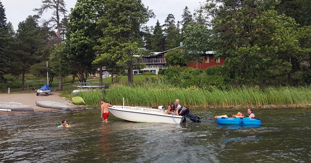 Båt vid strandkant med gröna träd och vass i bakgrunden