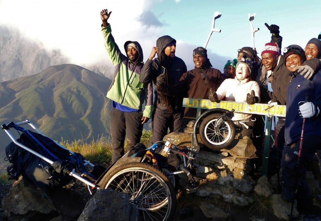 En grupp jublande personer på bergstopp.
