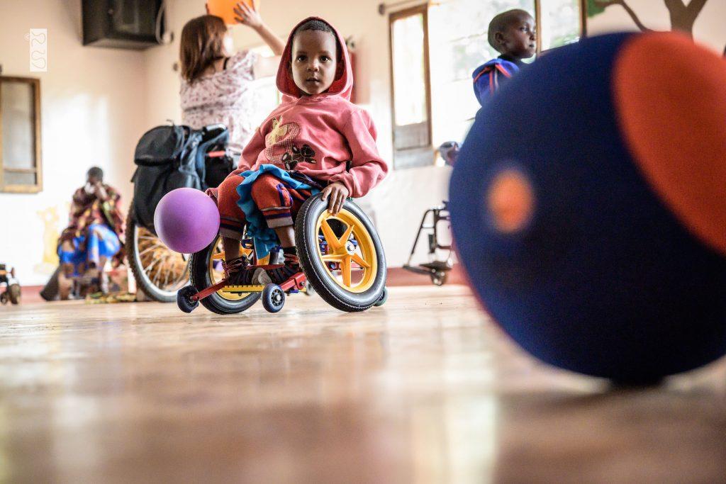 Lek och rörelse: barn i liten färgglad rullstol med människor i rörelse i bakgrunden