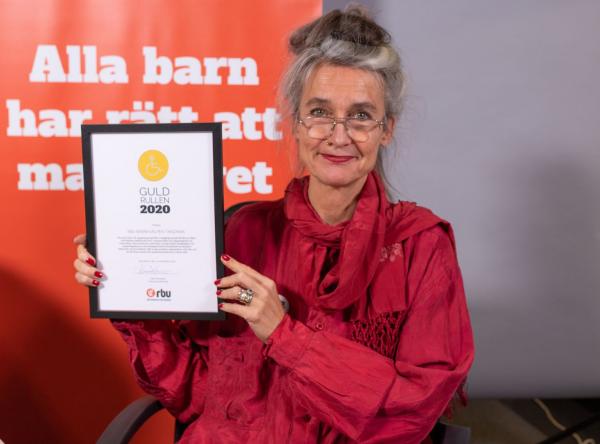 Förbundsordförande Maria Persdotter håller upp diplomet för Guldrullen 2020