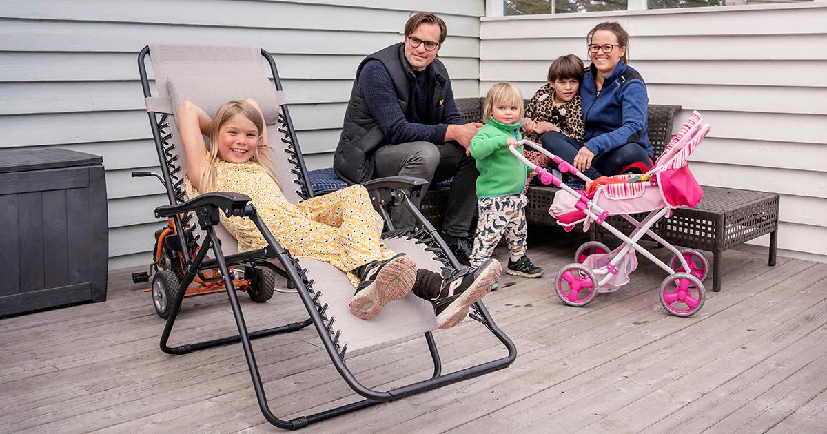 Två vuxna och tre barn sitter tillsammans på en altan och tittar glatt in i kameran.